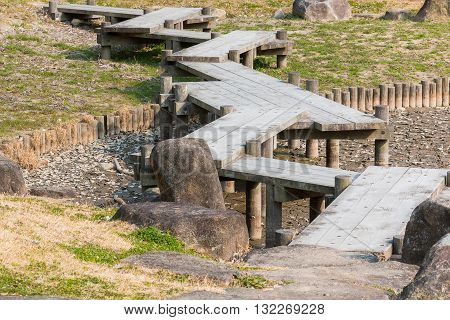 wooden bridge zigzagging on dry pond in Japanese garden. drought