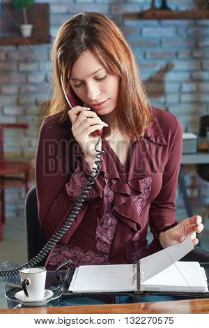 Young businesswoman talking on phone, looking at organizer.