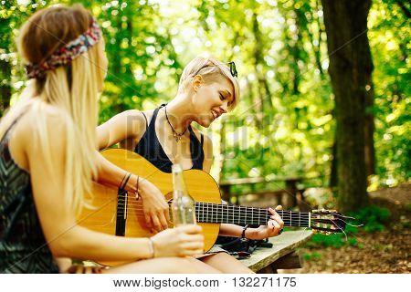Two woman traveler taking break in woods playing guitar and singing