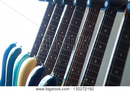 Electric guitars on a guitar rack by a sunlit window. Shallow depth of field.