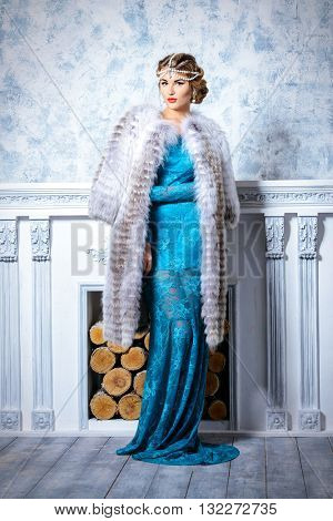 Full length portrait of a stunning young woman wearing evening dress and beautiful furs. Luxury, rich lifestyle. Jewellery. Fashion shot. Interior in classical style.