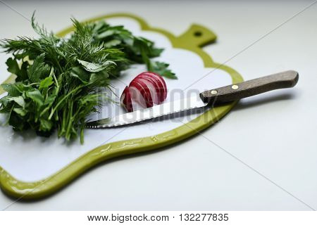 Greens, radish and a knife on choping board