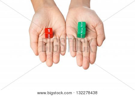Two hands holding fraction dices one hand with one red dice showing number one the other hand with two green dices showing one half numbers selective focus on dices on white background