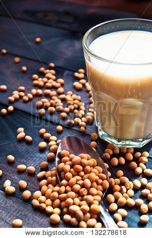 Glass of soy milk and soy beans on wooden background. Non-dairy milk