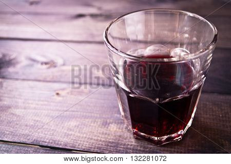 Unfinished glass of red wine on wooden bar table