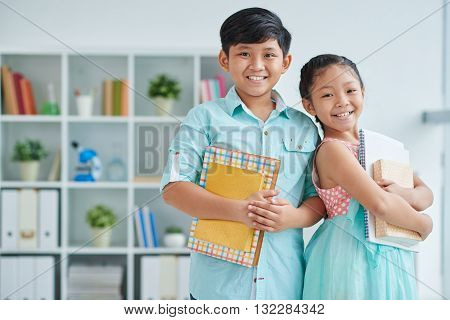 Portrait of happy Asian classmates with books looking at camera