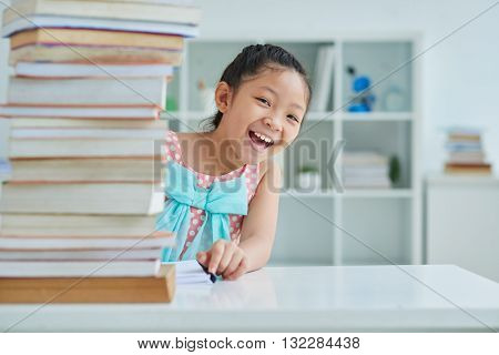 Happy cute Vietnamese girl looking out of big stack of books
