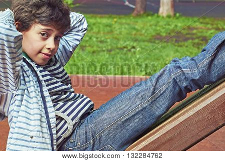 Handsome schoolboy doing an abdominal exercise outdoors