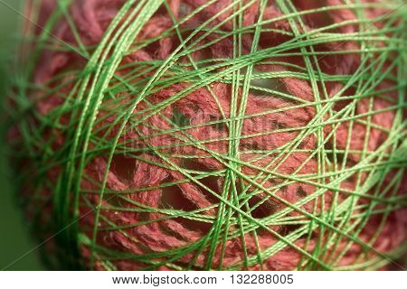 Glue yarn ball beautiful handmade decoration pink and green on blurred background