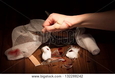 Fragments of broken glass, a wounded hand, bandages and adhesive tape on a black background.
