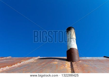 Old smoke pipe out of the rusty iron roof. In the background a clear blue sky.