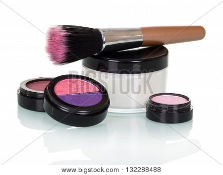 Cosmetic brush, eye shadow, blush and a jar of cream isolated on white background.