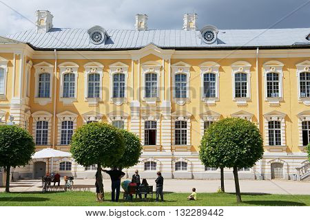 PILSRUNDALE, LATVIA - JULY 27, 2015: Unidentified people relax in front of the Rundale palace facade in Pilsrundale, Latvia.