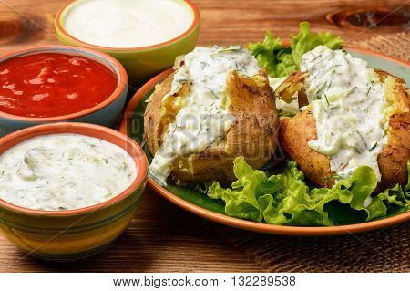 Jacket potatoes served with tzatziki sauce on wooden background..