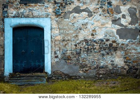 Old blue wooden door in stony building with textured wall and green grass background copy space