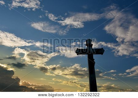 Christian wayside cross in front of cloudy sky in the evening after a thunderstorm
