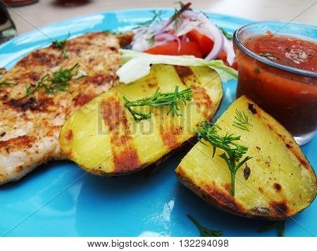 grilled meat with vegetables and salsa sauce on a blue plate