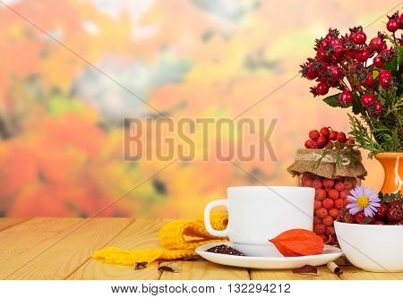 Rose hips and rowan berries, a cup of tea on a background of autumn leaves.