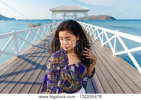 portrait asian woman long black hair with blue shawl and white jeans standing at wood bridge Asdang in SICHANG island Thailand landmark