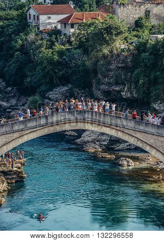 Mostar Bosnia and Herzegovina - August 25 2015. Tourists on Stari Most (english: Old Bridge) reconstructed 16th century Ottoman bridge main attraction of Mostar