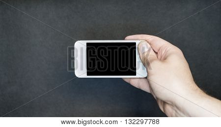 Man holding small smartphone sideways with free blank copy space for content
