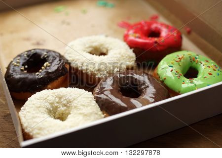 Colorful donuts in box, half-empty box, coconut topping
