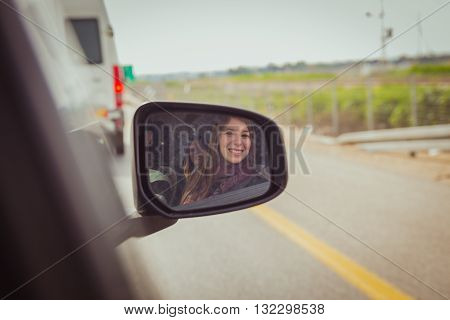 Women looking at the camera through the car side view mirror .