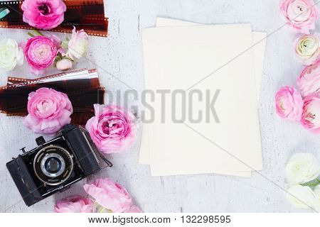 Ranunculus flowers with retro camera flat lay scene