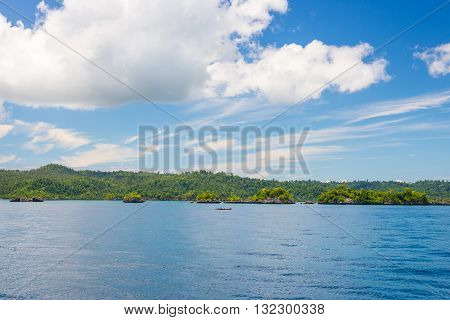 Rocky Coastline Of Island Spotted By Islets And Covered By Dense Lush Green Jungle In The Colorful S