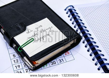 Black leather note book with a slogan on a note pad with calendar