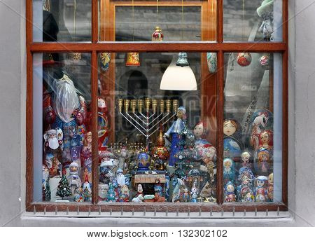 Prague, Czech Republic - April 13, 2016: A shop window in the Jewish quarter of Prague. Dolls toys Hanukkah candle behind the glass.