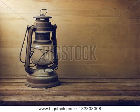 Vintage kerosen lamp on wooden table and wooden background