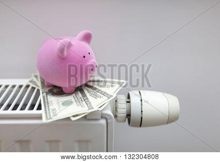 Piggy bank with american dollars on radiator. Energy saving concept.