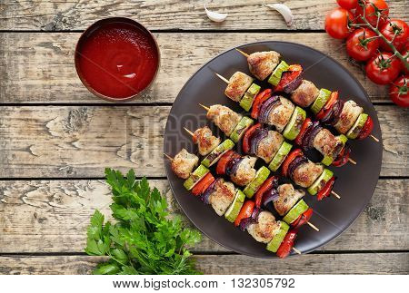 Turkey or chicken meat skewers shish kebab grilled food with onion, tomatoes, parsley and ketchup on rustic wooden table. Traditional barbecue shish