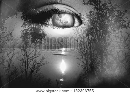 Halloween horror night background. Double exposure portrait of eye combined with silhouette of spooky forest with moon and river. Black and white picture style.