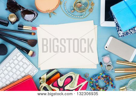 styled feminine desktop - woman fashion items on blue wooden background, copy space on aged photo paper