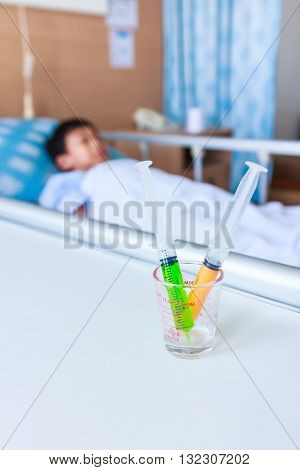 Syringes In A Glass Measuring Cup With Blurred Illness Boy Lying On Sickbed.