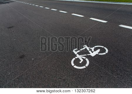 Pathway for bicycle with white bicycle lane sign on road. Bicycle sign path on road, bikes' lane on outskirts or urban area.