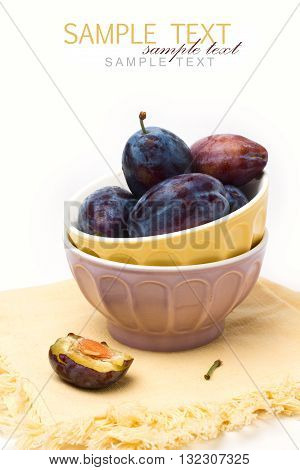 Fresh plumps in colorful bowls on white background