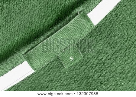 Blank green clothes label on green cloth as a background