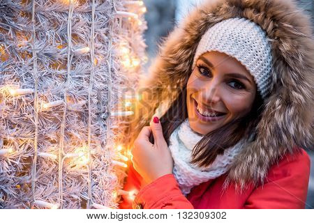 Portrait of a beautiful young woman next to a light gate on the christmas market.