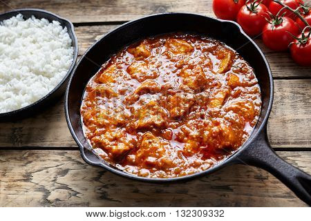 Traditional chicken tikka masala Asian national curry spicy meat meal with butter and rice in cast iron skillet on vintage wooden background.