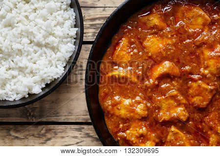 Chicken tikka masala traditional meat curry spicy food with rice in cast iron skillet on vintage wooden background
