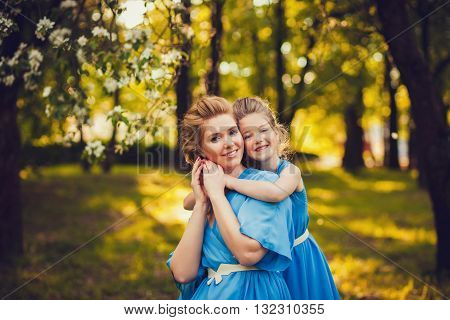 beautiful young mother and daughter in summer park