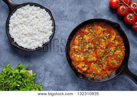 Chicken tikka masala traditional Asian spicy butter meat food with tomatoes, parsley and rice in cast iron skillet