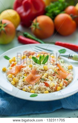 Fresh quinoa and cuscus salad with smoked salmon on plate