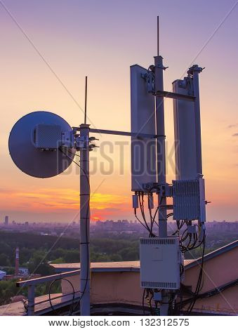 base station with a radio relay antenna on the background of a sunset over the city