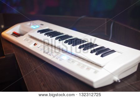 White synthesizer with black buttons on the table.