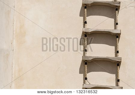 Ladder with rope hanged on a wall
