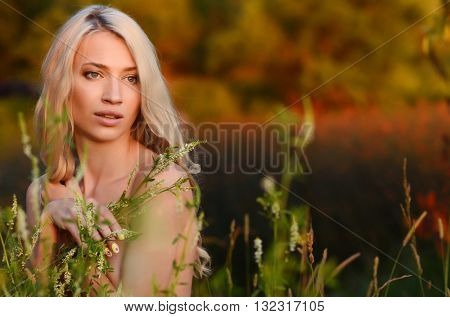 Blonde girl walking outdoor on the river bank at sunset.